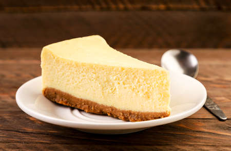 Cheesecake piece on a plate close-up on a wooden background