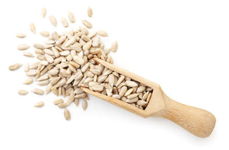 Sunflower kernels in a wooden scoop close up scattered on a white background, isolated. Top view
