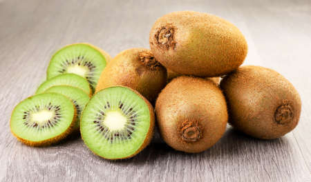Kiwi whole, halves and slices close-up on wooden background