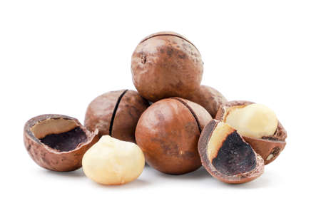 Heap of unpeeled and peeled macadamia nuts on a white background. Isolated