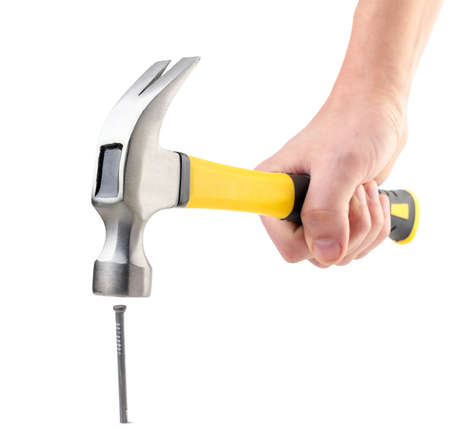 Hammer in hand hammering a nail close-up on a white background. Isolated Stock Photo