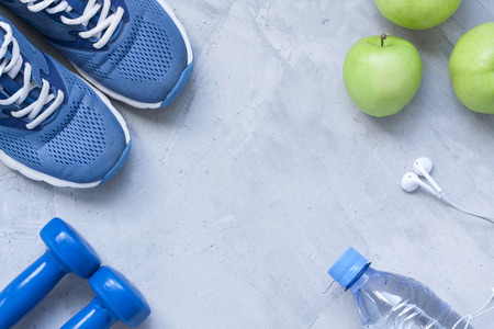 Flat lay sport shoes, dumbbells, earphones, apples, bottle of water on gray concrete background. Concept healthy lifestyle, sport and diet. Selective focus. Flat lay shot of Sport equipment. Imagens