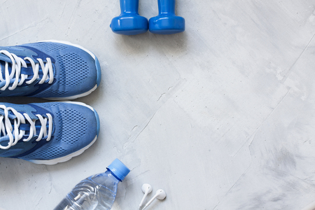 Flat lay sport shoes, bottle of water, dumbbells and earphones on gray concrete background. Concept healthy lifestyle, sport and diet. Focus is only on the sneakers. Sport equipment.