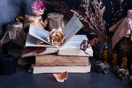 black magic: Witch accessories: old books, dry flowers and herbs, black candle, glass jars with drugs on dark background, low key