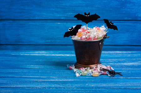 Halloween candy bucket, paper bats and rubber spider on blue wooden backround, horizontal orientation Stock Photo