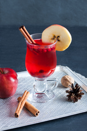 punch spice: Hot tea with cranberries, apple and cinnamon spices in glass cup on silver vintage tray