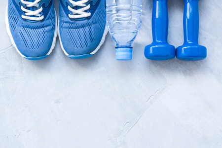 Flat lay sport shoes, bottle of water and dumbbells on gray concrete background. Concept healthy lifestyle, sport and diet.
