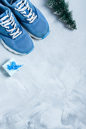 Christmas sport flat lay composition with shoes, christmas tree and blue gift box on gray concrete background. Concept ?hristmas special for healthy lifestyle and sport. Vertical orientation