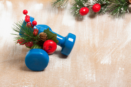 Christmas sport composition with dumbbells, red berries and spruce on plywood background. Concept ?hristmas special for healthy lifestyle and sport.