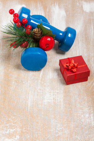 plywood: Christmas sport composition with dumbbells, red gift box, red berries, green spruce on plywood background. Concept ?hristmas special for healthy lifestyle and sport.