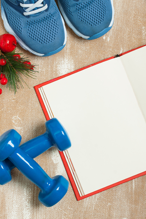 composition notebook: Christmas sport composition with blue sport shoes, blue dumbbells, red notebook and spruce branch with red berries. Concept christmas special for healthy lifestyle and sport. Flat lay, vertical orientation. Stock Photo
