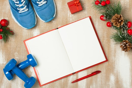 composition notebook: Christmas sport composition with blue sport shoes, blue dumbbells, red notebook, red small gift box, red pen and spruce branch with red berries and cones. Concept christmas special for healthy lifestyle and sport. Flat lay, horizontal orientation.