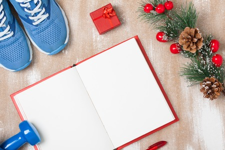 Christmas sport composition with blue sport shoes, blue dumbbells, red notebook, red small gift box, red pen and spruce branch with red berries and cones. Concept christmas special for healthy lifestyle and sport. Flat lay, horizontal orientation.