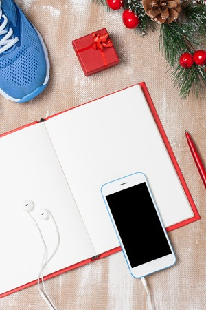 composition notebook: Christmas sport composition with blue sport shoes, red notebook, red small gift box, red pen, white smartphone with earfones and spruce branch with red berries and cones. Flat lay, vertical orientation. Stock Photo