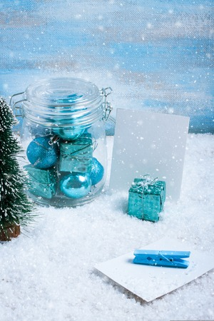 Glass jar with blue christmas decorations, blue gift box and paper for text or photo