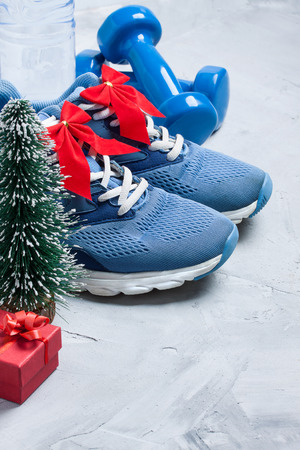 Christmas sport composition with blue sport shoes, blue dumbbells, red gift box, christmas tree and bottle of water on gray concrete background. Concept ?hristmas special for healthy lifestyle and sport.