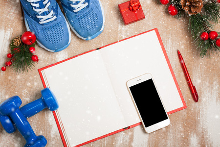 composition notebook: Christmas sport composition with blue sport shoes, blue dumbbells, red notebook, red small gift box, red pen, white smartphone with earfones and spruce branch with red berries and cones. Concept christmas special for healthy lifestyle and sport. Flat lay, Stock Photo