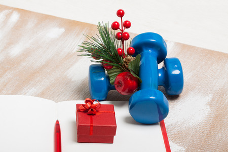 composition notebook: Christmas sport composition with dumbbells, red notebook, red berries and spruce on plywood background, flat lay. Concept Christmas special for healthy lifestyle and sport.