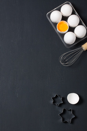 orientation: Dark wooden baking background with eggs, whisk, eggshell and star shape cookie  cutter. Vertical orientation with copyspace, top view.