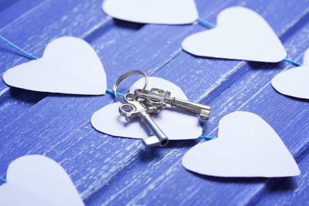 orientation: Paper hearts and silver keys on purple wooden background. Horizontal orientation, Close- up. Valentine background.