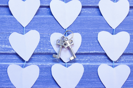 Paper hearts and silver keys on purple wooden background. Horizontal orientation, Close- up. Valentine background.
