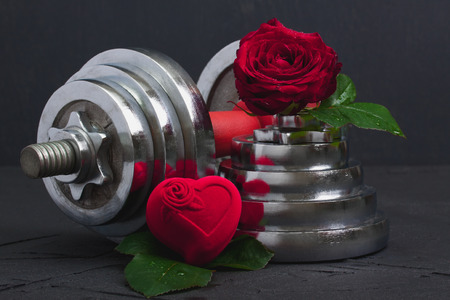 Valentines sports background with heavy dumbbell for workout, red rose with leaves and 