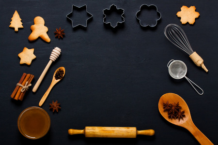 Dark wooden baking background with cookies, spice, honey and kitchen tools: rolling pin,  corolla, cookie cutter, spoons on dark wooden table. Horizontal orientation with copyspace,  top view.