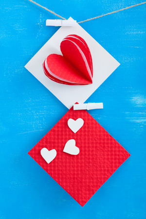 White gift card with paper hearts and red envelope on blue wooden background.