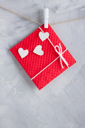 Red gift card wih white paper hearts hanging on the rope on gray concrete background. Vertical orientation, place for copyspace.