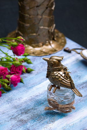 Steampunk bronze bird on glass cup, pink flowers, metallic hat on blue wooden tray. Stock Photo
