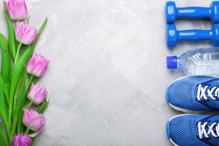 Spring flatlay sports composition with blue sneakers, dumbbells, bottle of water and purple tulips on gray concrete background. Concept healthy lifestyle, sport and diet in spring.