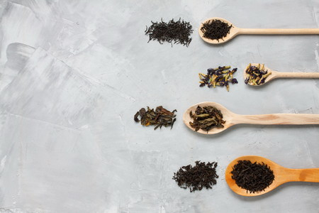 Four wooden spoons with different tea leaves: black, white, blue, green on grey  concrete background. Horizontal orientation, top view. Stock Photo