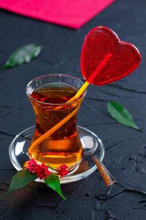 Glass with a tea, candy heart and silver spoon on black concrete background. Concept love, romantic.