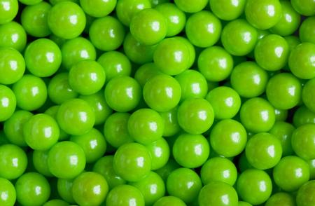 Modelo verde de dulces, caramelos de bola pegajosa para el fondo, puntos espolvorear el azúcar, la decoración de confitería. Macro, de cerca.