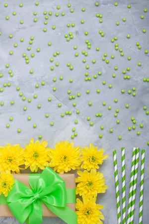 Gift box craft paper with green bow ribbon, yellow chrysanthemum flowers,  Stripped green paper straws for cocktails, decorating sugar balls on grey  concrete background. Vertical orientation, place for copyspace. Stock Photo