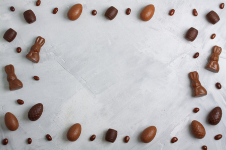 Chocolate easter eggs, rabbits, casks, sweets and candies on concrete background. Horizontal orientation, place for  copyspace, flatlay, top view.