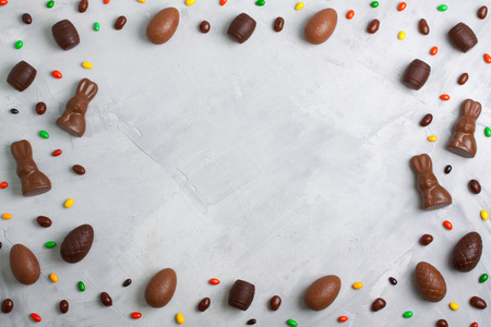 Chocolate easter eggs, rabbits, casks, sweets and colored candies on concrete background. Horizontal orientation, place for  copyspace, flatlay, top view.