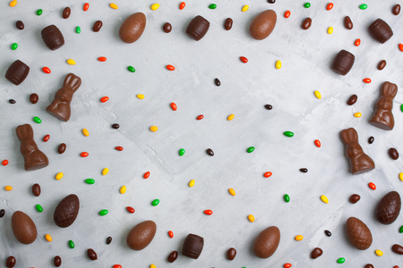 Chocolate easter eggs, rabbits, casks, sweets and colored candies pattern  on concrete background. Horizontal orientation,  place for copyspace, flatlay, top view. Stock Photo