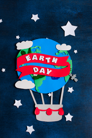 madre tierra: Paper craft earth globe, rocket, white stars, handmade on blue wooden background. Earth day  concept, lettering, text. Vertical orientation, top view.