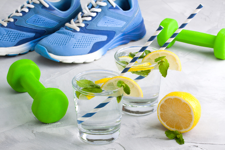 Sport composition with blue sneakers, green dumbbells, glasses of water with lemon, mint and straws on gray concrete  background. Concept healthy lifestyle, detox, diet.