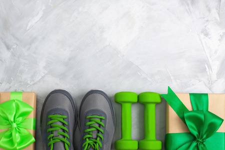 Holiday christmas birthday party sport flat lay composition with gray shoes, green dumbbells and craft gifts with green bow on gray concrete background. Top view, horizontal orientation