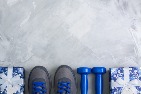 Holiday christmas birthday party sport flat lay composition with gray shoes, blue dumbbells 