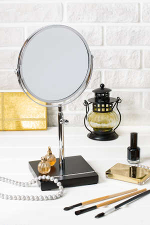 Cosmetic set: perfume, essence, pearl, cream, nail polish, eyeshadow, rouge, brushes, beauty accessories  on white wooden table and white painted brick wall background. Beauty, fashion composition concept,  vertical orientation.