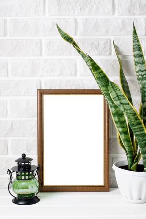 A4 poster mock-up in wooden frame, sansevie three-striped, candlelight on white wooden table and white  painted brick wall background. Vertical orientation, place for copyspace.