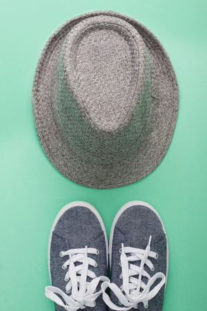 Women's flat lay clothes gray hat and gray sneakers on a cyan background. Fashion blog, clothing, shopping concept, top view, vertical orientation.