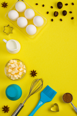 Baking background with eggs, butter, milk, spices cocoa, soda, anise, nutmeg, coffee beans and kitchen tools rolling    pin, wooden spoons, whisk, sieve, bake ware shape cookie cutter on yellow background. Stock Photo