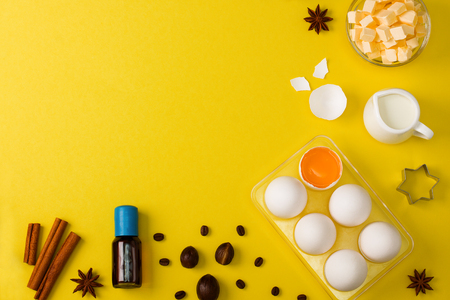 Baking background with eggs, butter, milk, spices cocoa, soda, anise,    nutmeg, coffee beans and kitchen tools rolling pin, wooden spoons,    whisk, sieve, bake ware shape cookie cutter on yellow background.