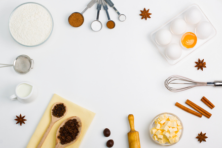 Cooking baking flat lay background with eggs, yolk, a cup of butter, a cup of flour, milk, spices 