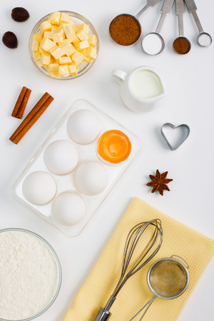 Cooking baking flat lay background with eggs yolk a cup of butter flour milk    spices cinnamon anise nutmeg and kitchen tools sieve whisk measuring spoons.    Vertical orientation, place for copy space.