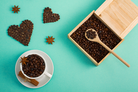 Cup of coffee seeds, cinnamon, anis coffee heart shapes, wooden box and spoon with coffee  
